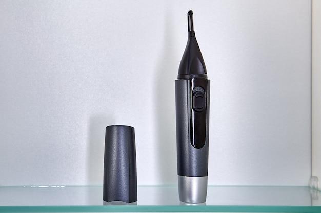 Il rifinitore cordless per sopracciglia, orecchie e narici si trova su un ripiano di vetro nell'armadietto del bagno