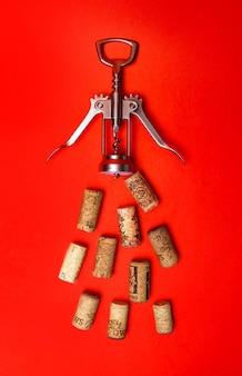 Cavatappi per vino e tappi su fondo rosso