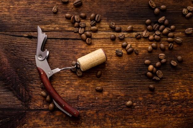 Cavatappi con un tappo di sughero su uno sfondo di legno con chicchi di caffè.