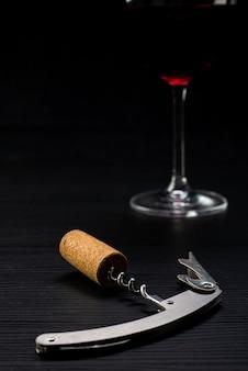 Cavatappi con un tappo di vino e un bicchiere sfocato sullo sfondo
