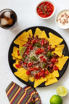 Nachos di patatine di mais con carne, formaggio, pomodori e peperoni. cibo messicano. cucina nazionale.