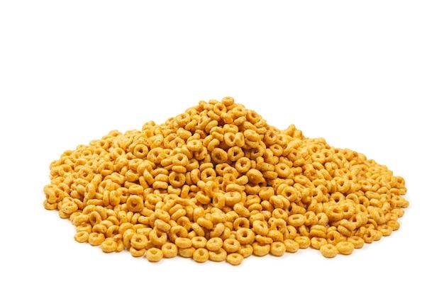 Sfondo e consistenza dei fiocchi di mais. vista dall'alto. scatola di cereali con anelli di miele per la colazione del mattino.