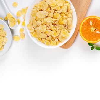 I fiocchi di mais ciotola dolci con latte e arancia su sfondo bianco, close up, concetto di design colazione fresca e sana.