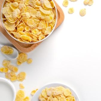 Ciotola di fiocchi di mais con latte e arancia su sfondo bianco, vista dall'alto, layout piatto sopra la testa, concetto di design per una colazione fresca e salutare.