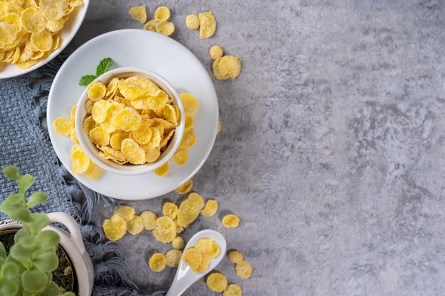 I fiocchi di mais ciotola dolci sul tavolo di cemento grigio