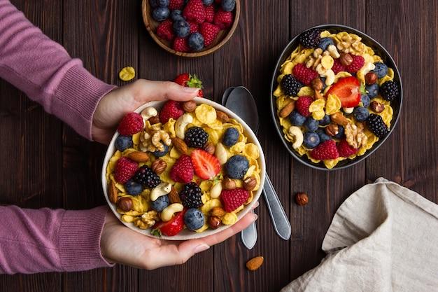 Fiocchi di mais in una ciotola con frutti di bosco e mano femminile su fondo in legno. vista dall'alto di una sana colazione.