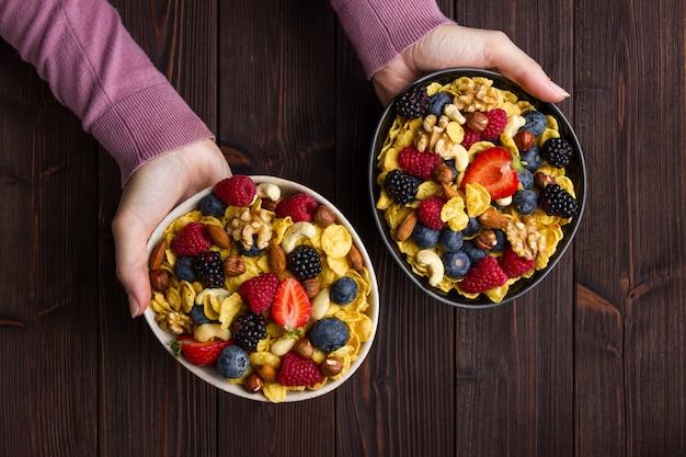 Fiocchi di mais in una ciotola con frutti di bosco e mani femminili su fondo di legno. vista dall'alto di una sana colazione.