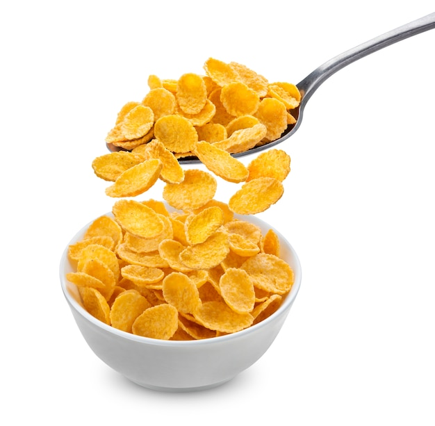 Fiocchi di mais che cadono dal cucchiaio nella ciotola