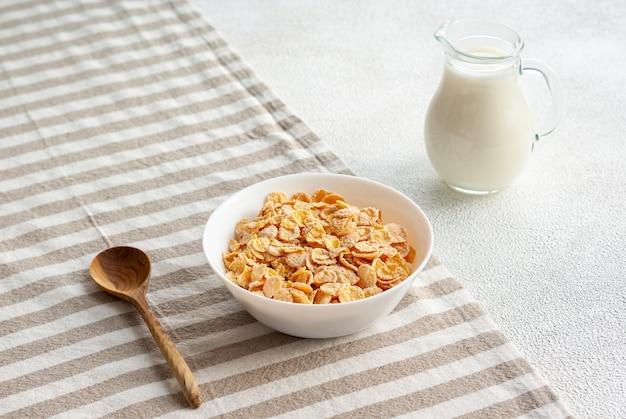 Fiocchi di mais con un barattolo di latte su un tavolo, colazione semplice