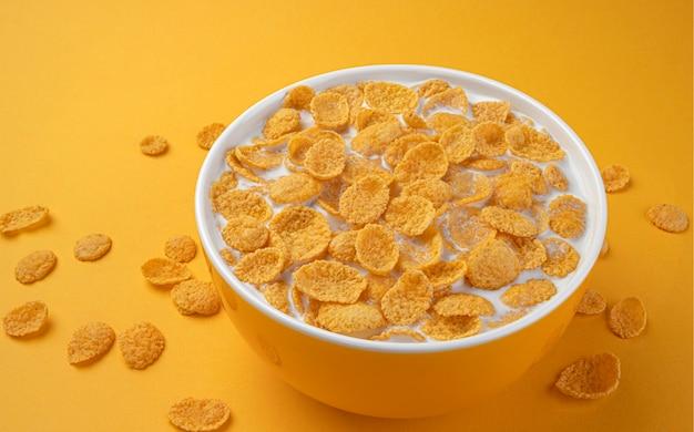 Fiocchi di mais con latte, ciotola blu di sana colazione a base di cereali