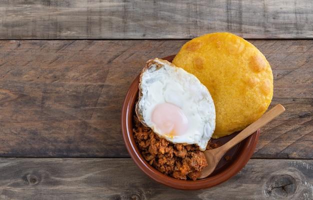 Frittelle di mais con carne macinata e uovo fritto. cucina tipica spagnola. copia spazio.