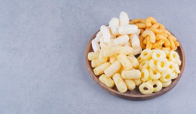 Anelli di mais e bastoncini di mais in un piatto di legno sulla superficie di marmo