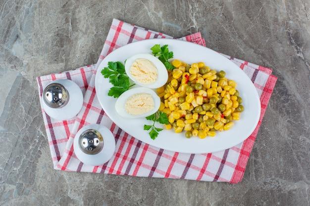 Insalata di mais e uovo a fette su un piatto accanto al sale su un canovaccio, sulla superficie di marmo. .