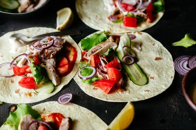 Tortillas di mais ripiene di pollo e verdure su un tavolo di legno cottura dei tacos