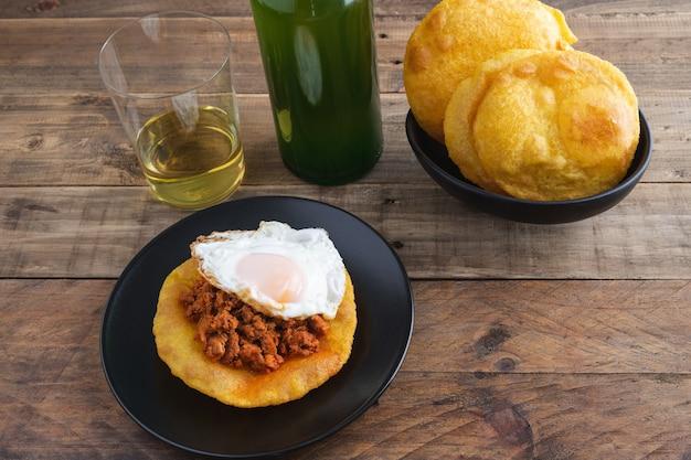 Tortos di mais con picadillo e uovo fritto. bottiglia e bicchiere di sidro asturiano. cucina tipica asturiana. copia spazio.