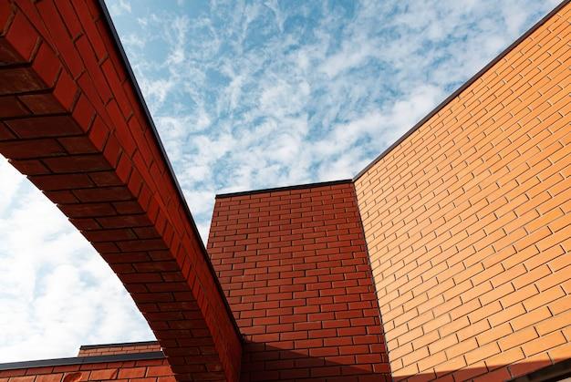 Angolo di un edificio in mattoni con archi su uno sfondo di cielo azzurro con nuvole