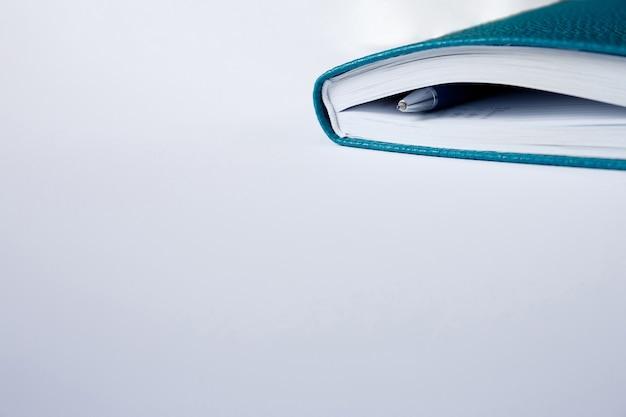 Coperchio d'angolo del taccuino, diario o libro blu con la penna su carta bianca