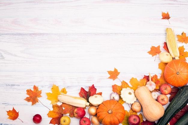 Disposizione ad angolo con zucca, mais, altre verdure e foglie d'autunno. vista dall'alto su uno sfondo di legno chiaro. autunno laici piatta.