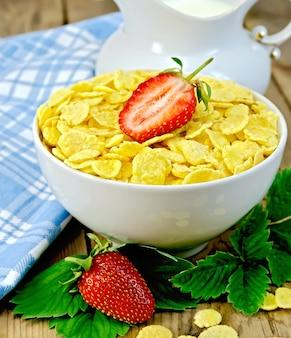 Fiocchi di mais in una ciotola bianca, foglie e fragole, latte in una brocca, un tovagliolo sullo sfondo di tavole di legno