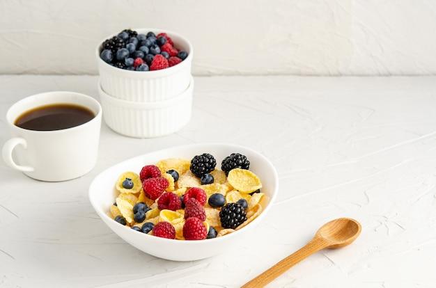 Cornflakes con latte e frutti di bosco freschi su una superficie bianca