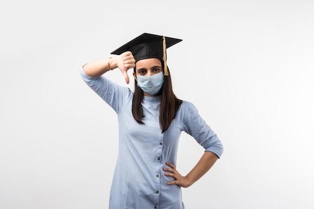 Corona pandemia e confusione sugli esami universitari in india - bella studentessa indiana con espressioni confuse che indossano maschera medica e cappello da laurea