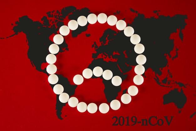 Coronavirus 2019-ncov nuovo concetto di coronavirus responsabile dell'epidemia di influenza asiatica come pandemia di casi di ceppi influenzali pericolosi. faccina triste fatta di compresse bianche e mappa su sfondo rosso.