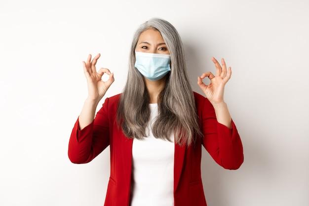 Coronavirus e concetto di business. manager femminile asiatico in maschera facciale che sembra allegro, mostrando segni di approvazione, sfondo bianco.