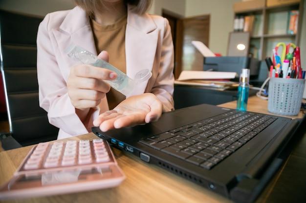 Coronavirus. donna d'affari, lavoro da casa. lavorare da casa. lavarsi le mani con un gel disinfettante.