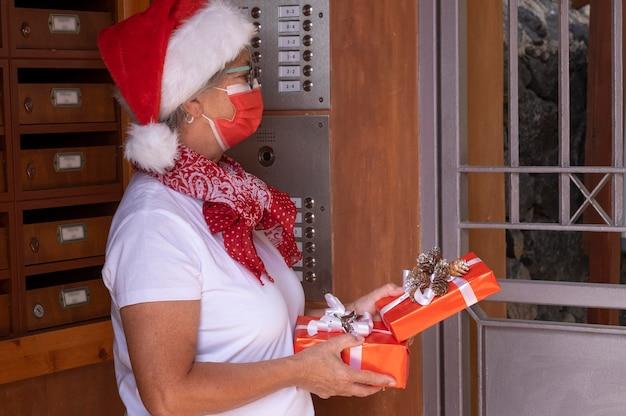 Coronavirus e natale 2020. una donna messaggera senior che indossa un cappello da babbo natale e una maschera medica per evitare l'infezione da coronavirus che consegna regali di natale a casa