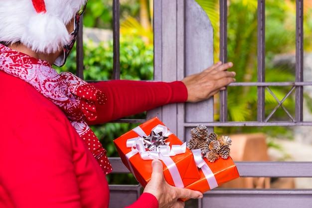 Coronavirus e natale 2020. donna anziana che indossa una maschera protettiva per il viso a causa del coronavirus in attesa alla porta per consegnare i regali di natale. una donna con il cappello di babbo natale