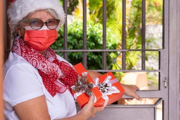 Coronavirus e natale. una donna messaggera anziana che indossa un cappello da babbo natale e una maschera medica per evitare l'infezione da coronavirus che consegna regali di natale a casa