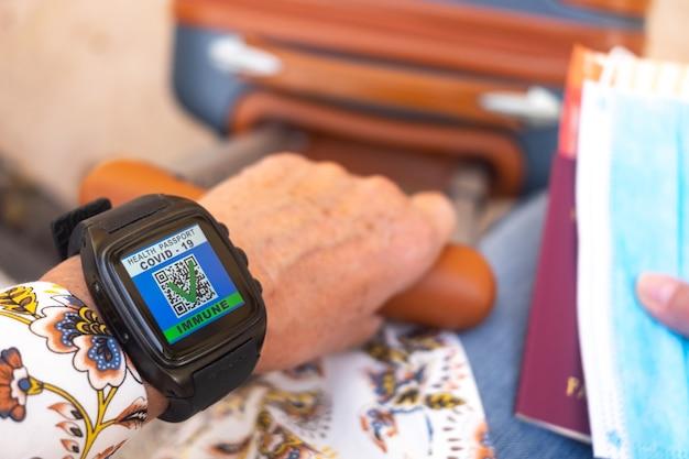 Coronavirus. primo piano di una donna con bagagli e documenti per il viaggio, che indossa un orologio da polso con certificato digitale di vaccinazione contro covid-19. persone immunizzate