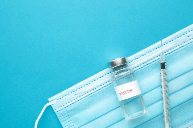 Coronavirus o covid-19, 2019 - vaccino ncov in bottiglia con siringa e maschera protettiva per l'igiene su sfondo blu. vista dall'alto