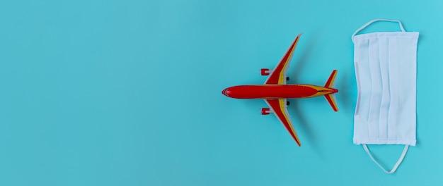Concetto di situazione di volo di coronavirus covid-19. maschera facciale e giocattolo rosso aereo su sfondo azzurro con copyspace, flatlay, banner