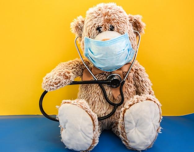 Coronavirus covid-19 e concetto di protezione dall'inquinamento. orsacchiotto di peluche bambola che indossa la maschera e il fonendoscopio, uno stetoscopio, copia spazio, cure mediche,