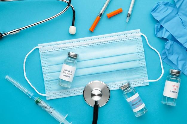 Fiale di vaccino coronavirus covid-19, siringa, guanti medicali e stetoscopio su sfondo blu. sessione di vaccinazione e miglioramento dell'immunità. vista superiore del covid 19