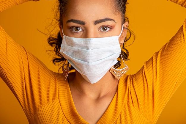 Coronavirus (covid-19. giovane donna che indossa una maschera, guardando la fotocamera, da vicino, isolato. epidemia di influenza, allergia alla polvere, protezione da virus. concetto di inquinamento dell'aria della città.
