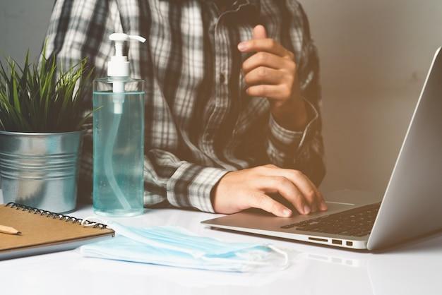 Malattia da coronavirus o concetto di protezione covid-19 - il giovane lavora nella stanza dell'ufficio a casa con attrezzature protettive e di pulizia per proteggersi dal virus corona mentre utilizza il computer portatile alla scrivania.