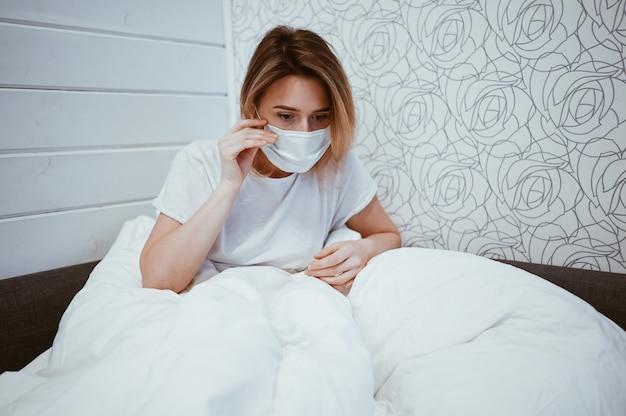 I sintomi della coronavirus (covid-19) sono naso che cola, mal di gola, tosse e febbre. giovane donna malata di infezione virale da coronavirus che diffonde il virus corona. paziente sdraiato nel letto di casa in quarantena