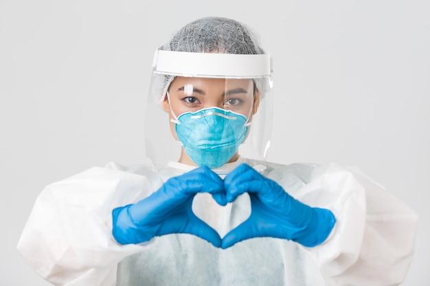 , malattia da coronavirus, concetto di operatori sanitari. primo piano del medico femminile asiatico fiducioso e premuroso in dispositivi di protezione individuale, che mostra il gesto del cuore ai pazienti