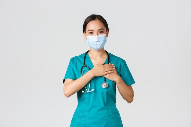 , malattia da coronavirus, concetto di operatori sanitari. medico femminile asiatico premuroso amichevole, medico in maschera medica e guanti, mano nella mano sul cuore e muro bianco e sorridente