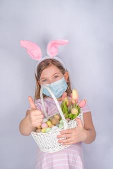 Coronavirus e vacanze di pasqua. bambina sveglia in una mascherina medica protettiva con le orecchie del coniglietto. priorità bassa della bandiera di pasqua. con le uova di pasqua e la merce nel cestino del fiore di primavera
