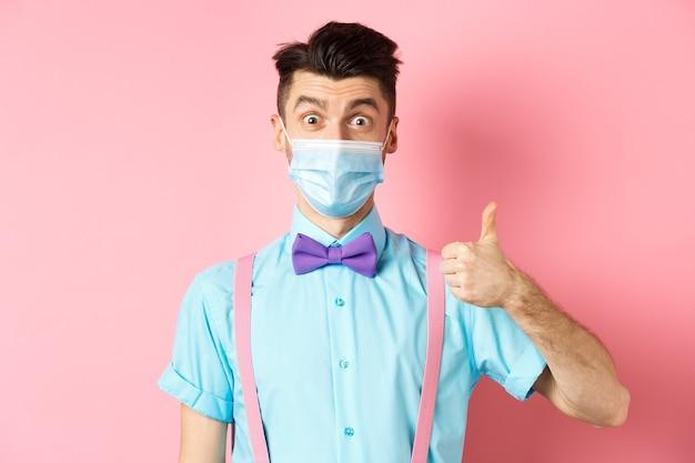 Coronavirus, assistenza sanitaria e concetto di quarantena. giovane impressionato nella mascherina medica che mostra il pollice in su, sembrante soddisfatto, consigliando un buon prodotto, sfondo rosa.