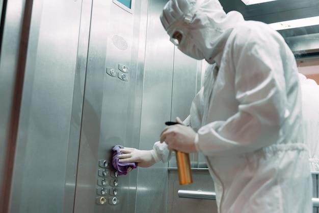 Infezione da coronavirus. paramedico in maschera protettiva e costume che disinfetta un ascensore con spruzzatore,