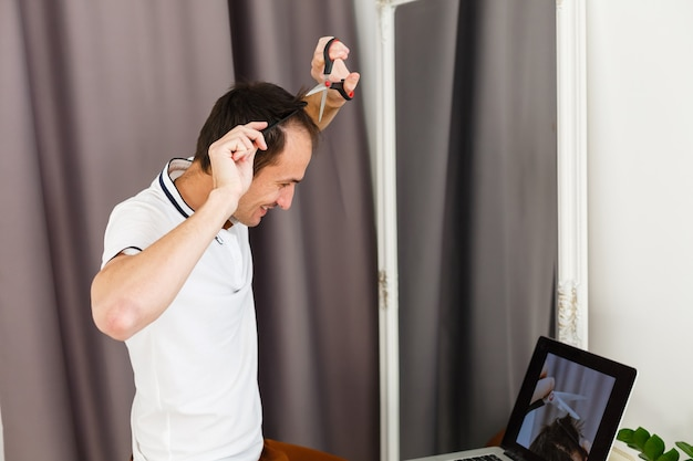 Taglio di capelli da uomo coronavirus a casa, lezioni di parrucchiere online su un laptop