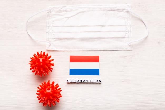 Maschera respiratoria protettiva con vista dall'alto del concetto di coronavirus ncov e sulla bandiera dei paesi bassi