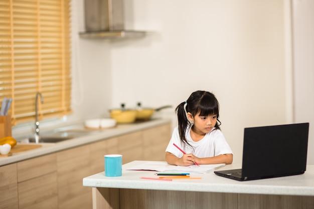 Epidemia di coronavirus. chiusura e chiusura delle scuole. studentessa che guarda la lezione di educazione online, parla felice con l'insegnante su internet a casa. la pandemia di covid-19 costringe i bambini all'apprendimento online