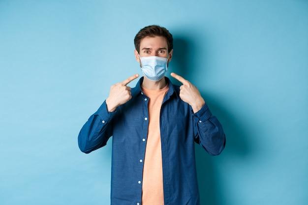 Coronavirus e concetto di pandemia. ritratto di uomo felice e sano che punta il dito contro la sua maschera medica, sorridendo alla telecamera, in piedi su sfondo blu.