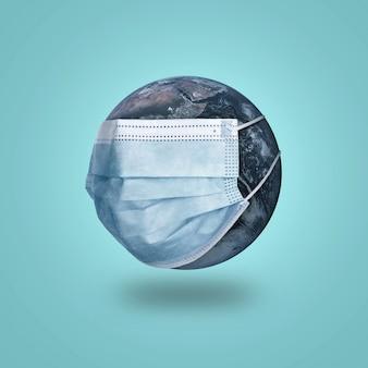 Concetto di pandemia di coronavirus covid-19. pianeta terra in una maschera protettiva medica su un blu.