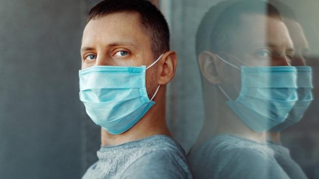 Coronavirus pandemia covid-19 e concetto di quarantena. uomo in una mascherina medica vicino alla finestra.